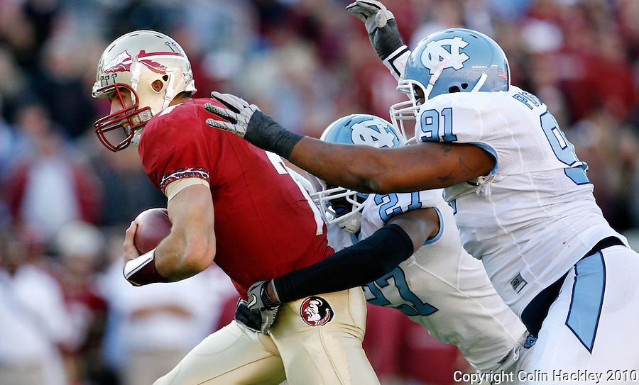 TALLAHASSEE, FL 11/6/10-FSU-NC FB10 CH-Florida State's Christian Ponder is pulled down by North Carolina's Da'Norris Searcy, left, and Tydreke Powell at the end of a 14 yard scramble during first half action Saturday at Doak Campbell Stadium in Tallahassee. The Tar Heels beat the Seminoles 37-35. .COLIN HACKLEY PHOTO