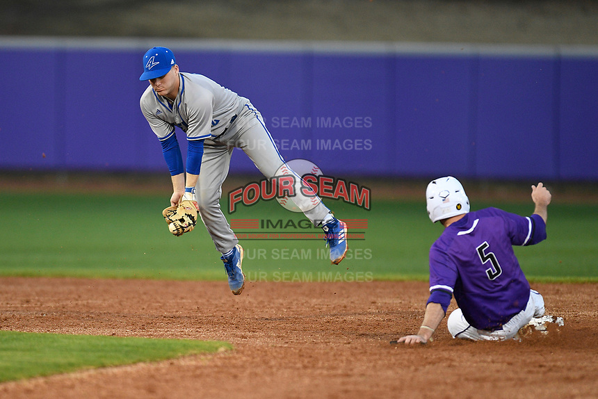 Right fielder David Webel (5) of the Furman Paladins is safe at second on a wild pitch as UNC Asheville second baseman Chris Troost (2) grabs an errant throw in a game on Wednesday, February 27, 2019, at Latham Baseball Stadium on the Furman University campus in Greenville, South Carolina. UNC Asheville won, 4-3. (Tom Priddy/Four Seam Images)