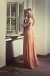 young woman with blonde hair standing at an old window and wearing a vintage dress