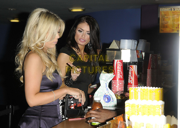 Frankie Essex & Chloe Simms .Turnout - UK film premiere, Genesis Cinema, Mile End Road, London, England..September 12th, 2011.half length black top white snakeskin skirt print purple sleeveless dress side profile candy food counter popcorn side profile .CAP/CAN.©Can Nguyen/Capital Pictures.
