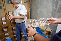 "NWA Democrat-Gazette/DAVID GOTTSCHALK Rob Mullins (right), Public Works Manager with the city of Eureka Springs, displays an estimated 1928 automobile license plate Friday, June 29, 2018, as Mayor Robert ""Butch"" Berry looks at pages of newspapers at the Public Works building in Eureka Springs. The two vehicles and other objects of antiquity, including newspaper pages, were discovered during an excavation of a site at Main and Flint Streets in Eureka Springs. The excavation is taking place during storm water drainage repairs."