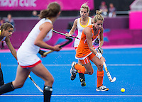 29 JUL 2012 - LONDON, GBR - Eva de Goede (NED) of Netherlands (right, in orange) looks for a way through the Belgian defence during their women's London 2012 Olympic Games Preliminary round hockey match at the Riverbank Arena in the Olympic Park in Stratford, London, Great Britain (PHOTO (C) 2012 NIGEL FARROW)