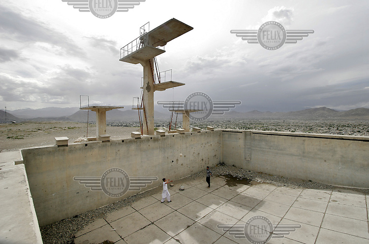 Children play in a pool on a hill where taleban used to execute people. Kabul, Afghanistan.