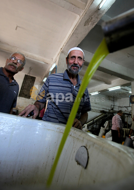 Fresh oil is seen at after crush olive at an olive press in the West bank city of Nablus October 16, 2016. Photo by Nedal Eshtayah