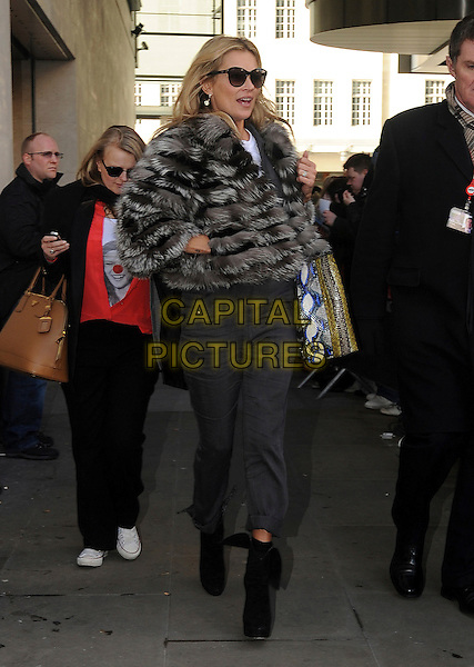 Kate Moss.Celebrities at BBC Radio 1 promoting Comic Relief Red Nose Day, London, England..March 14th, 2013.full length brown fur jacket sunglasses shades hand in pocket grey gray jumpsuit boots blue snakeskin bag purse .CAP/AOU.©AOU/Capital Pictures.