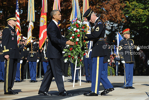 United States President Barack Obama positions a commemorative wreath during a ceremony to honor veterans at the Tomb of the Unknowns at Arlington National Cemetery on November 11, 2013 in Arlington, Virginia. <br /> Credit: Olivier Douliery / Pool via CNP