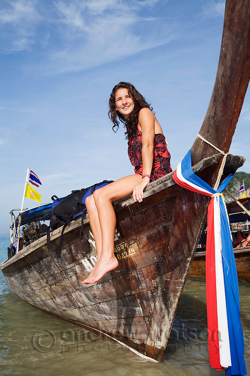 A young woman sits on the bow of a longtail boat moored at Hat Rai Leh West , Krabi province, THAILAND.  (Model Released)