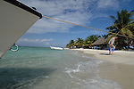 Boat anchors on remote beach on barrier island off Belize, man carries snorkel gear..