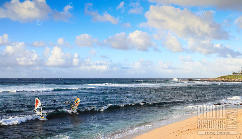 Windsurfers and surfers make the most of the waves at Ho'okipa Beach on Maui.