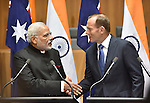AUSTRALIA, Canberra : Indian Prime Minister Narendra Modi (L) shakes hands with Australian Prime Minister Tony Abbott (R) after a press conference at Parliament House, Canberra on November 18, 2014. AFP PHOTO / MARK GRAHAM