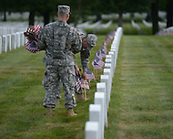 May 23, 2013  (Arlington, Virginia)  Members of the 3rd U.S. Infantry Regiment (the Old Guard), place American flags before a gravestone at Arlington National Cemetery. The annual tradition, known as Flags In, honors every fallen soldier's grave with a flag.  (Photo by Don Baxter/Media Images International)