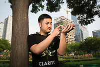 Wei Zheng, 31, with his juvenile Blue Iguana (Cyclura lewisi) in Beijing's CBD area. The species, also known as the Grand Cayman iguana, is endemic to the Cayman Islands in the Caribbean and is listed as 'Endangered' on the IUCN Red List. It is estimated there are only approximately 750 individuals left in the wild with the main causes of disappearance being human induced factors including habitat destruction from agriculture and urban development.