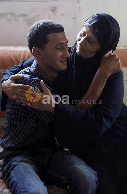 Ahmed Obaid, 18, a mentally disabled Palestinian youth, hugs his mother at their home in Issawiya neighborhood in Jerusalem on 02 September 2013. Israeli security forces arrested Obaid during a protest against killing of three Palestinians in Qalandiya refugee camp. He was released on bail on Monday after spending a week in jail under torture. Photo by Saeed Qaq