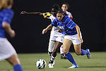 20 September 2012: Duke's Mollie Pathman (right) is held by Maryland's Shade Pratt (behind). The University of Maryland Terrapins played the Duke University Blue Devils to a 2-2 tie after overtime at Koskinen Stadium in Durham, North Carolina in a 2012 NCAA Division I Women's Soccer game.