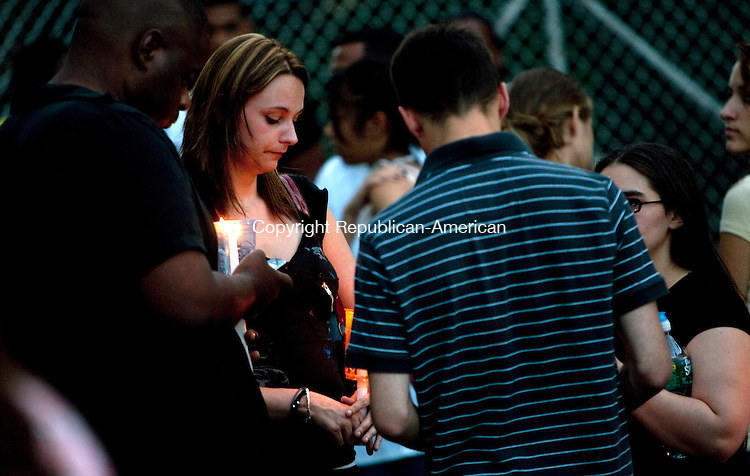 WATERBURY, CT 18  JULY, 2010-07180JS05-A man lights a candle at a makeshift memorial as friends and family members garthered at the gates of Holy Land USA in Waterbury on Sunday for a candle light vigil to pay their respects for 16-year-old Chole Ottman whose body was discovered there on Saturday. Waterbury police have charged Francisco Cruz, 19, with her murder. <br /> Jim Shannon Republican-American