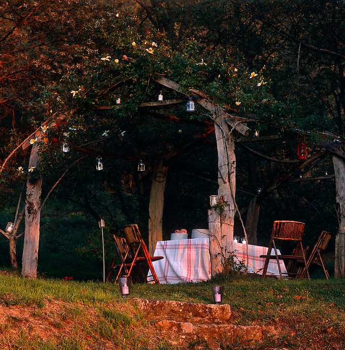 A dining table and garden chairs under a rustic rose arbour in the warm light of the setting sun
