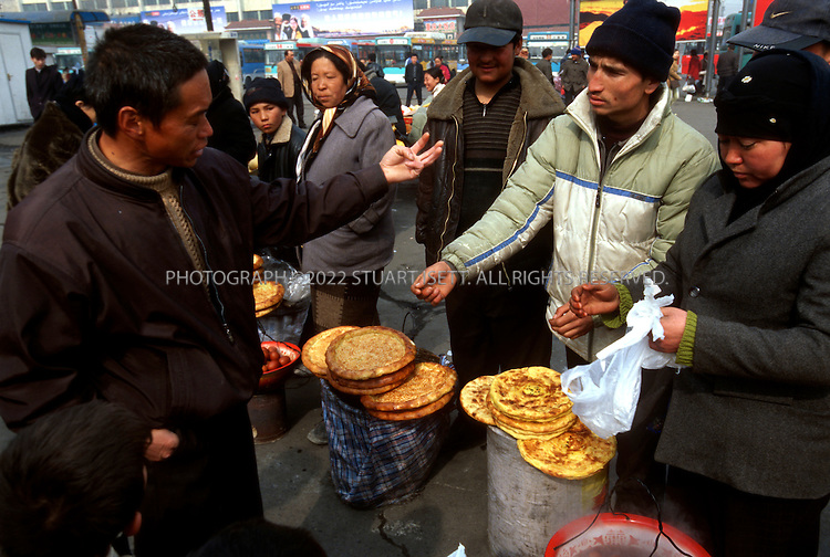 3/8/2004--Urumqi, Xinjiang Province, China..Uighur food vendors argue with a Han Chinese immigrant at Urumqi Station over prices. The rise of a Urumqi,  the capital of Xinjiang, has barely papered over the ethnic and religious cracks that run deep in this region, which sits astride the ancient Silk Road, where Islam has reigned supreme for 1,000 years, but is now under heavy pressure from massive Han Chinese migration, breakneck development and often heavy-handed government repression. In today?s Xinjiang, money, authority, power and many Uighurs say, hope too, are all firmly in the grasp of the Han, who arrive from poorer areas of China by the thousands every day to seek their fortunes here. The restive Uighurs, a Central Asian ethnic group common to this part of China and to the neighboring former Soviet republics, meanwhile, are becoming an increasingly voiceless minority in their own homeland...Photograph by Stuart Isett.©2004 Stuart Isett
