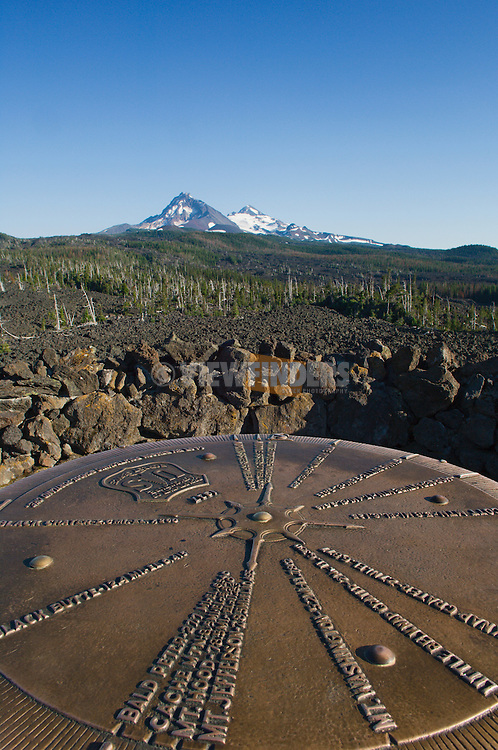 Bronze plaque pointing out mountain peaks seen from Dee Wright Observatory at McKenzie Pass in the Cascade Mountains of Oregon, with North Sister and Middle Sister volcanic peaks in the distance.