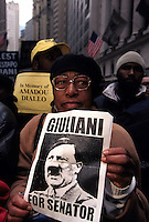 (020216-SWR01.jpg) 3 Mar 99 - New York, NY -- A woman carrying a mock campaign poster of senatorial candidate and New York CityMayor Rudy Giuliani depicted as Adolph Hitler, was among thousands of protesters who rallied on Wall Street to protest the plice killing of Afircan immigrant Amadou Diallo.