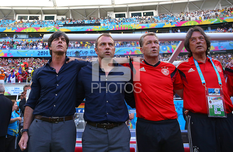 Germany coach Joachim Loew (left) and his coaching team sing their national anthem before kick off