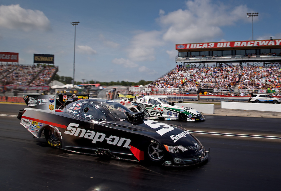 Sept. 1, 2013; Clermont, IN, USA: NHRA funny car driver Cruz Pedregon (near lane) races alongside John Force during qualifying for the US Nationals at Lucas Oil Raceway. Mandatory Credit: Mark J. Rebilas-