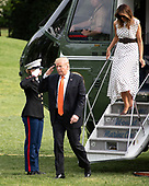 United States President Donald J. Trump, accompanied by First lady Melania Trump, salutes the Marine Guard as they arrive on the South Lawn of the White House in Washington, DC after delivering remarks at the Prescription Drug Abuse and Heroin Summit in Atlanta, Georgia on April 24, 2019.<br /> Credit: Ron Sachs / CNP