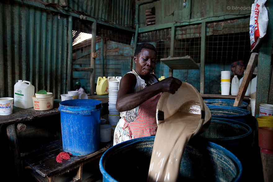 Mary working at the Madiaba Busaa Club in a Nairobi slum on april 7, 2013. Mary has been selling Busaa, a traditional fermented beer, for many years. Busaa is made by crudely fermenting maize, millet, sorghum or molasses. At Kshs 35 per liter it is much cheaper than a Kshs120 half-liter bottle of commercial beer. The local brew was legalised in 2010 and since then busaa clubs have become increasingly popular. Drinking is on the rise in Kenya, especially among young people. Photo by Benedicte Desrus