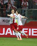 Krzystof Maczynski scores the opener for Poland and celebrates