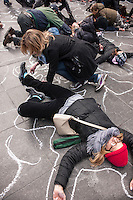 "Several hundred performing arts professionals, members of the theater community and their supporters participate in ""flash mob"" performance in Times Square, Sunday, February 24, 2013 against gun violence. The group lay down on the ground drawing chalk outlines around themselves reminiscent of police crime scenes, then writing the names of the victims of the Newtown Ct. shooting within. The performance was created by choreographer Lorin Latarro and the performers also held hand over their partners' heart for 26 seconds for the 26 victims in Newtown. (© Richard B. Levine)"