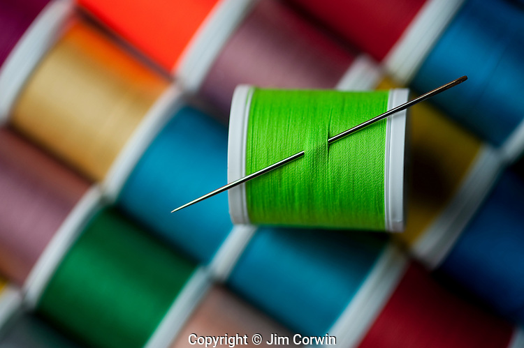 Bright colored spools of thread with sewing needle