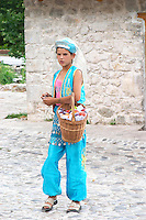 Girl in traditional costume selling fruit to visitors. Pocitelj historic Muslim and Christian village near Mostar. Federation Bosne i Hercegovine. Bosnia Herzegovina, Europe.
