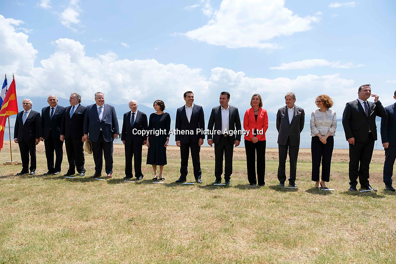 Pictured: Greek Prime Minister Alexis Tsipras with his counterpart Zoran Zaevat (both C) with other dignitaries at Prespa Lake in northern Greece. Sunday 17 June 2018<br /> Re: Greece and the Former Yugoslav Republic Of Macedonia (FYROM) have signed a deal that aims to settle a decades-long dispute over the country's name.<br /> Under the agreement, Greece's neighbour will be known as North Macedonia.<br /> Heated rows over Macedonia's name have been going on since the break-up of the former Yugoslavia, of which it was a part, and have held up Macedonia's entry to Nato and the EU.<br /> Greece has long argued that by using the name Macedonia, its neighbour was implying it had a claim on the northern Greek province also called Macedonia.<br /> The two countries' leaders, Mr Tsipras and his Macedonian counterpart Zoran Zaev announced the deal on Tuesday and have pressed ahead despite protests.<br /> The two countries' foreign ministers signed the deal on Lake Prespa on Greece's northern border on Sunday.<br /> The agreement still needs to be approved by both parliaments and by a referendum in Macedonia.