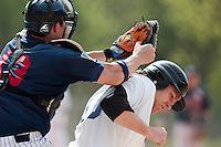 25 April 2010: Boris Marche of Rouen tags out Nicolas Dubaut of the PUC at homeplate during game 1/week 3 of the French Elite season won 12-4 by Rouen over the PUC, at the Pershing Stadium in Vincennes, near Paris, France.