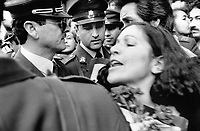 Policemen surround a woman during a rally by relatives of disappeared political prisoners.