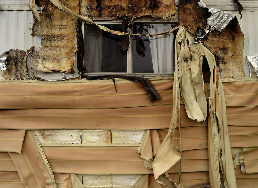 Melted siding sags off a mobile home which was next door to a mobile home that burned to the ground in the Napa Valley Mobile Home Park after a magnitude 6.0 earthquake struck in the early morning of August 24, 2014, in Napa, California. after a magnitude 6.0 earthquake struck in the early morning of August 24, 2014, in Napa, California.