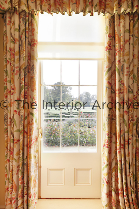 A door onto the garden is draped with curtains patterned with fruit in shades of orange, yellow and red