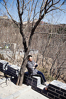 A woman leans against a tree at the Badaling entrance to the Great Wall outside of Beijing, China.