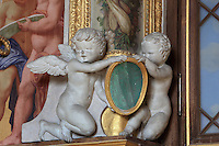 Putti holding a medallion in carved stucco from the frame of the Diana fresco by Rosso Fiorentino, 1535-37, in the Galerie Francois I, begun 1528, the first great gallery in France and the origination of the Renaissance style in France, Chateau de Fontainebleau, France. The Palace of Fontainebleau is one of the largest French royal palaces and was begun in the early 16th century for Francois I. It was listed as a UNESCO World Heritage Site in 1981. Picture by Manuel Cohen