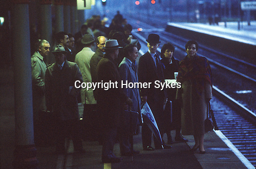 Train commuters wait at Grantham railway station for the train to London. City business man wears a blower hat. 1980s England Uk