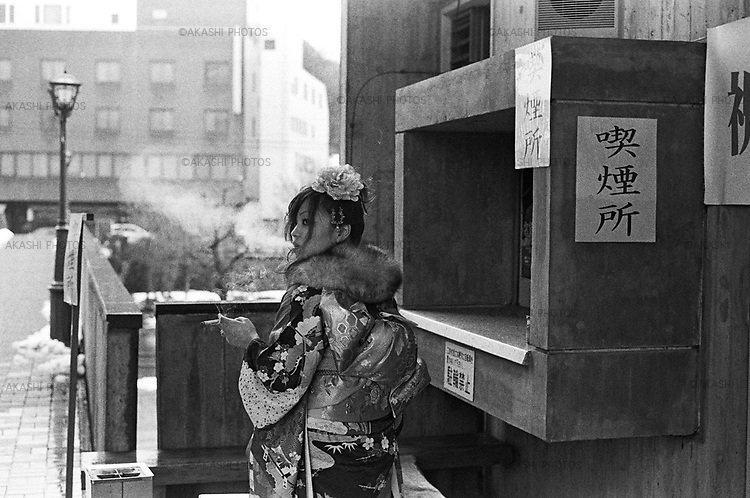 A Japanese woman in kimono smokes before she enters the hall for a coming-of-age ceremony in Toyoka City Hall. In Japan, in every January, men and women who become 20 years old celebrate the ceremony in each city hall where they grew up.