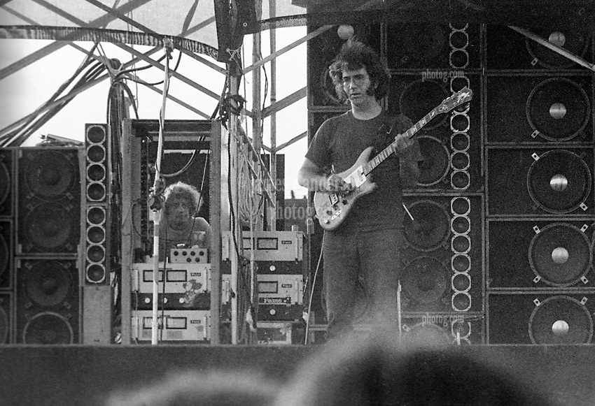 Jerry Garcia performing with The Grateful Dead. In Concert at Dillon Stadium on 31 July 1974. During the first set or beginning of the second set. This image is a cropped version of the full frame film scan and thus displays more inherent film grain. Photograph shot with a Nikon FTn Camera and Kodak Tri-X B&W Film.