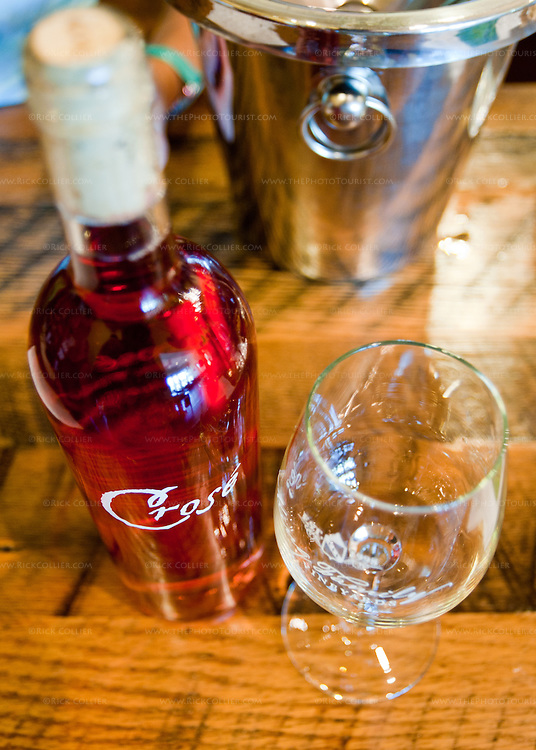 A bottle of rose wine and a glass stand ready for a tasting on the wood tasting bar at King Family Vineyards.