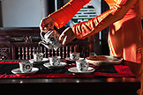 VIETNAM, Hue, Ms. Boi Tran's Hoang Vien restaurant, a woman in traditional dress pours tea
