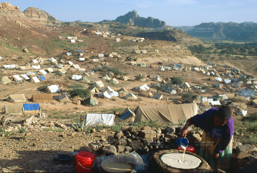 "Eritrea. Southern Debud Zone. Maiwuray. People and families live in tents, because they are IDP (Internaly Displaced People) from the war on a border dispute(1999 to 2001) between Eritrea and Ethiopia. Early morning, a woman cooks the local bread ""injera""  on an oven.© 2002 Didier Ruef"