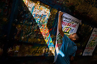"""A Colombian sign painter apprentice takes down a just-finished music party poster in the sign painting workshop in Cartagena, Colombia, 12 December 2017. Hidden in the dark, narrow alleys of Bazurto market, a group of dozen young men gathered around José Corredor (""""Runner""""), the master painter, produce every day hundreds of hand-painted posters. Although the vast majority of the production is designed for a cheap visual promotion of popular Champeta music parties, held every weekend around the city, Runner and his apprentices also create other graphic design artworks, based on brush lettering technique. Using simple brushes and bright paints, the artisanal workshop keeps the traditional sign painting art alive."""