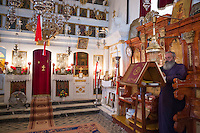 Greek Orthodox priest reading bible inside chapel of christian church at Krini, Corfu, , Greece