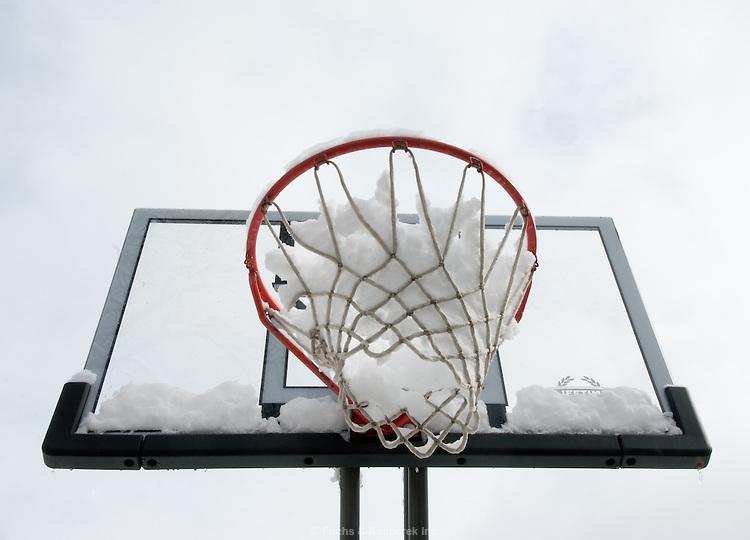 A basketball hoop in winter.