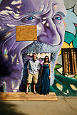 USA, Los Angeles, a couple standing in front of a wall mural on the side of a building on Abbot Kinney Boulevard