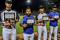 Members of the Columbia Fireflies hold signs honoring family and friends on Stand Up To Cancer night during a game against the Lexington Legends on Thursday, June 13, 2019, at Segra Park in Columbia, South Carolina. Lexington won, 10-5. (Tom Priddy/Four Seam Images)
