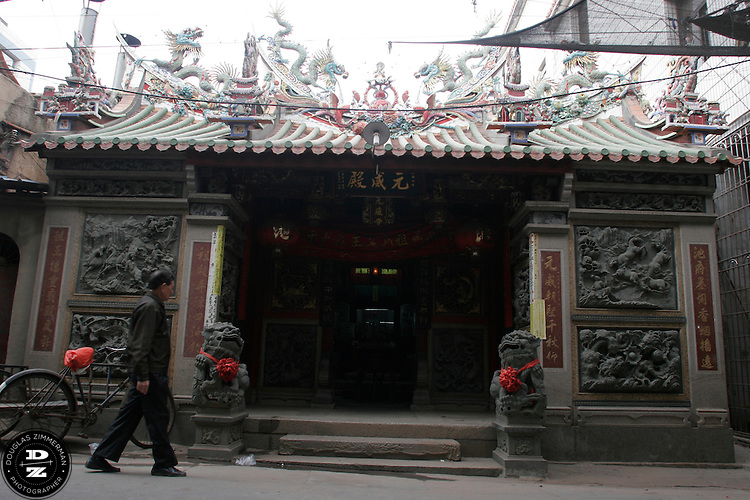 A man walks into the Qi Temple along the main street of Maxiang, China.  The village of Maxiang,  north of the city of Xiamen, has grown from a small village into a large suburb over the past several years as construction and industry have arrived in the area.  Photograph by Douglas ZImmerman